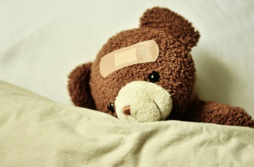 Illness - Teddy bear under blankets with a plaster on his head